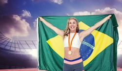 Athlete posing with gold medal after victory against race track