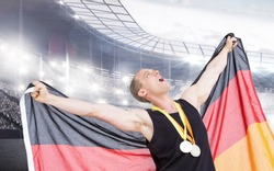 Athlete posing with olympic gold medals around his neck against sports arena