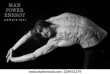 Athlete.Power.Energy.Gym.Men\'s sports figure on a black background.Exercise.Black-and-white image.