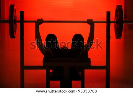 Athlete raising the bar black silhouette on red background