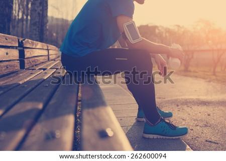 Athlete restin on bench in park at sunset after running with bottle of water (intentional sun glare and vintage color)
