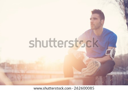 Athlete resting on the bench in park with bottle of water, armband with mobile phone and listening music (intentional sun glare and vintage color)