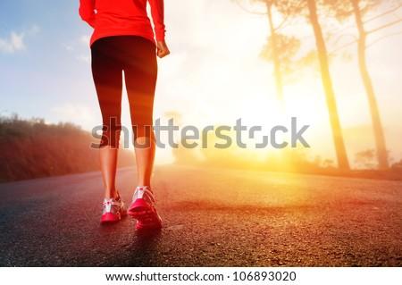 Athlete runner feet running on road closeup on shoe. woman fitness sunrise jog workout wellness concept.