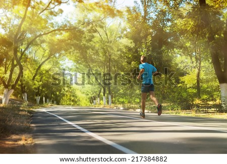 Athlete runner feet running on the road.Mans fitness with the sun effect  in the background and open space around him