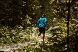 athlete runner in blue sports jacket forest trail in rain