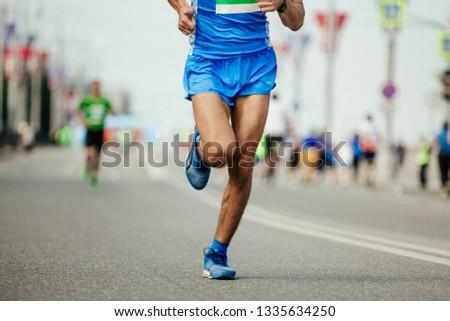 athlete runner in blue sportswear running marathon race on city #1335634250