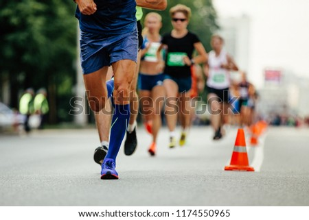 athlete runner in compression socks running ahead group of runners #1174550965