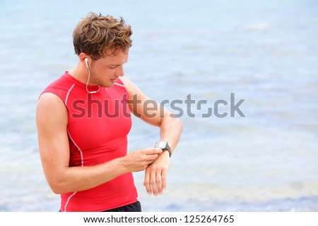 Athlete runner looking at heart rate monitor watch. Man running on beach taking a break in compression t-shirt top.
