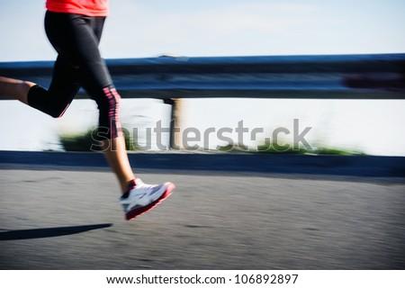 athlete runner motion blur running on road focus on shoe