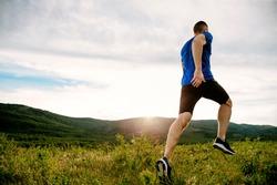 athlete runner run on mountain trail in summer sunset
