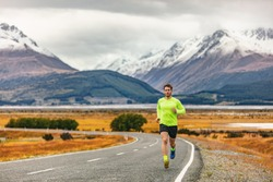 Athlete runner running road race in amazing mountain range landscape in New Zealand. Man run exercise long distance cardio training outdoors in cold fall weather.