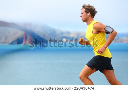 Athlete running man - male runner in San Francisco listening to music on smartphone. Sporty fit young man jogging by San Francisco Bay and Golden Gate Bridge. Jogger training with smart phone armband, #220438474