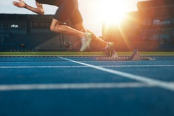 Athlete running on athletic racetrack. Low section shot of male runner starting the sprint from the starting line with bright sunlight.