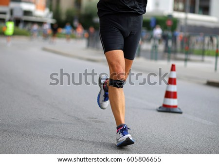 athlete running with bandage on his knees during the marathon in the city #605806655