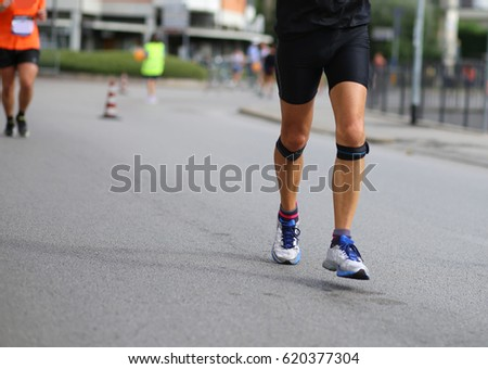 athlete running with bandage on his knees during the marathon in the city #620377304