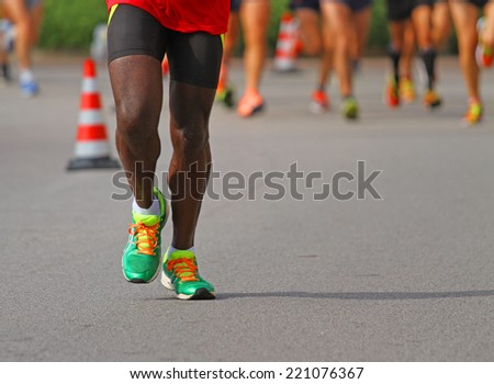 athlete runs down the street during the race outdoors with other people #221076367