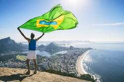 Athlete stands holding a Brazilian flag at a bright overlook of the city skyline of Rio de Janeiro, Brazil
