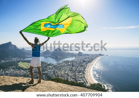 Athlete stands holding a Brazilian flag at a bright overlook of the city skyline of Rio de Janeiro, Brazil #407709904