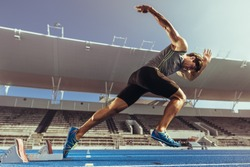 Athlete starting his sprint on an all-weather running track. Runner using starting block to start his run on running track in a stadium.