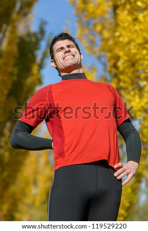 Athlete suffering from back pain or kidney problem. Sportsman with painful sport injury.