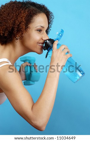 Athlete taking a break at the gym for a quick drink from her water bottle