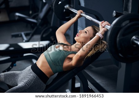 Athlete tensing her hands muscles while lifting a weight over her head on a gym press bench Photo stock ©