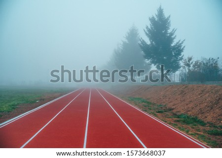 Athlete Track or Running Track in autumn nature. Blue misty background. White edit space