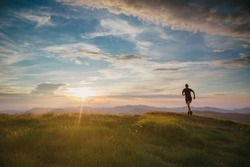 Athlete trailrunning in the mountains during a nice sunset. With motion blur and old film effect.