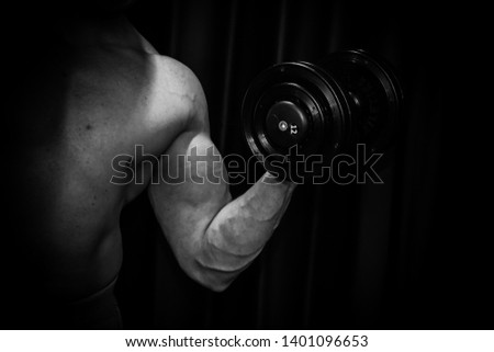 athlete trains biceps hands with dumbbells in the center of workouts on a black background. training tools in the gym close-up.