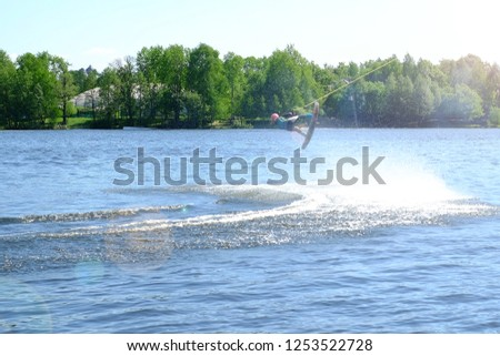 Athlete wakeboarder performs a jump with a somersault in the air #1253522728