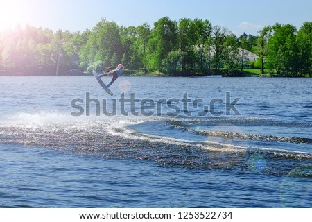 Athlete wakeboarder performs a jump with a somersault in the air #1253522734