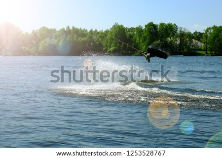 Athlete wakeboarder performs a jump with a somersault in the air #1253528767