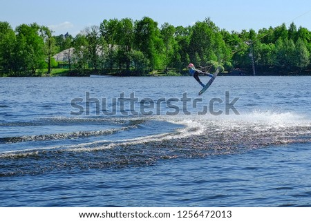 Athlete wakeboarder performs a jump with a somersault in the air #1256472013