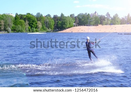 Athlete wakeboarder performs a jump with a somersault in the air #1256472016
