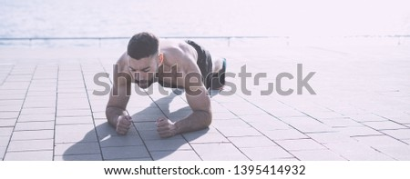 Athlete with fit muscular body practicing plank shirtless. Fitness outdoors #1395414932