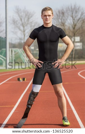 Athlete with handicap stands on a race track - stock photo