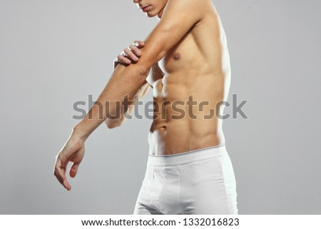 athlete with muscled muscles touches his hand white briefs gray background