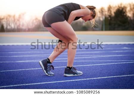 Athlete woman has calf crump, pain in leg during running