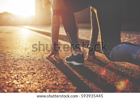 Athlete woman in running start pose on the city street. Sport tight clothes. Bright sunset, blurry background. Horizontal - Shutterstock ID 593935445