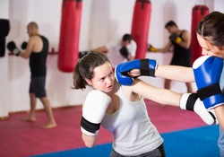 Athlete woman is having sparring with partner in the boxing hall.