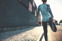Athlete woman preparing for running on the city street. Legs warming and stretching. Sport tight clothes. Blurry background. Horizontal