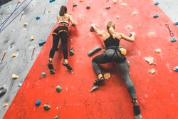 Athletes climber moving up on steep rock, climbing on artificial wall indoors. Extreme sports and bouldering concept