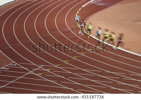 Athletes in motion on professional track and field race. Nice picture for olympic game in Rio