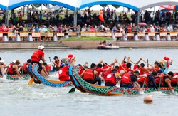 Athletes pulling vigorously on the oars in a competitive boat racing on Keelung River & spectators on the riverbank cheering for their teams in the traditional Dragon Boat Festival in Taipei, Taiwan