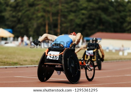 athletes racers on wheelchair racing and athletics track #1295361295
