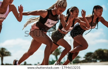 Athletes starting off for a race on a running track. Female runner starting a sprint at stadium track. Foto stock ©