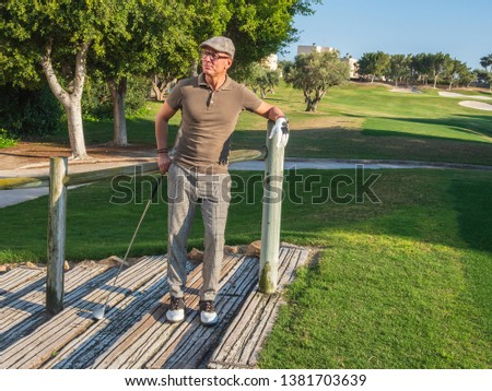 athletic and attractive man playing golf on a sunny day #1381703639