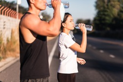 Athletic Asian couple wearing face mask drinking water on road after exercising together during coronavirus or covid-19 outbreak. Putting off protective masks. Work out in quarantine.