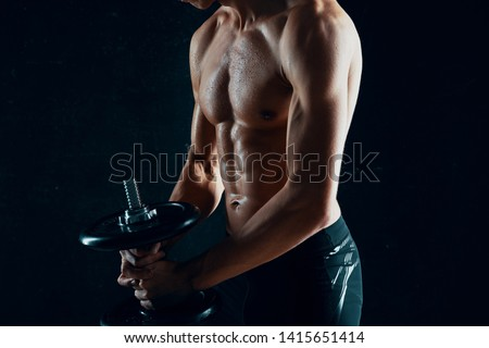 Athletic athletic male athletes muscular  dumbbells in the hands of a workout gym biceps bodybuilder