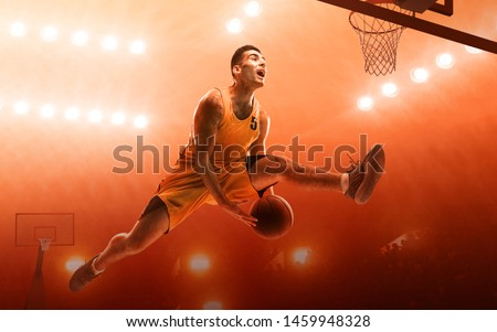 Athletic basketball player scoring a layup basket during a professional basketball game. Red floodlit background